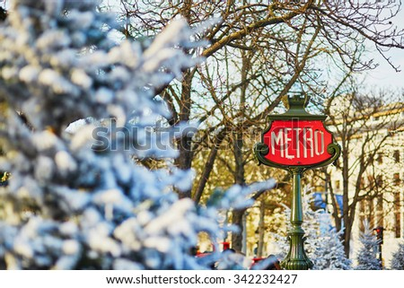 Parisian metro sign and trees covered with snow - stock photo