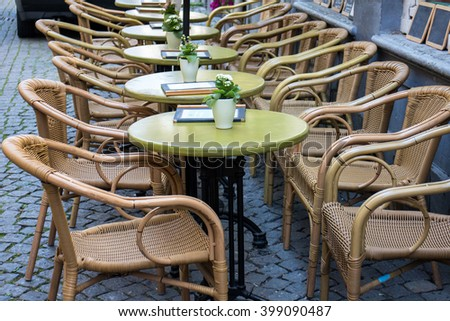 Parisian restaurant terrace with empty tables and chairs - stock photo