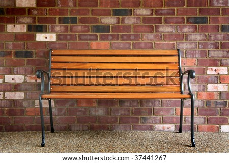 Park bench against a brick wall - stock photo