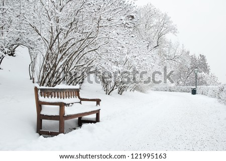 Park bench and trees covered by heavy snow - stock photo