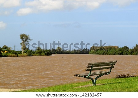 Park bench beside brown flooded river - stock photo