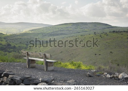 Park bench gazes at a cloud covered Tiberius hillside - stock photo