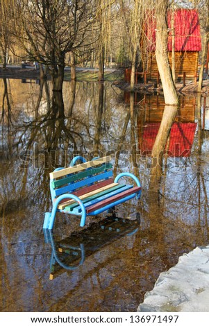 Park bench in flood water - stock photo