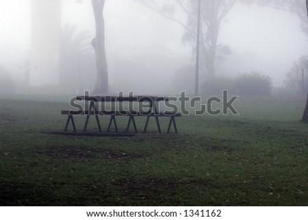 Park bench in mist - stock photo