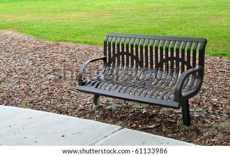 Park bench made of metal. Painted brown and surrounded by concrete, leaves and grass. - stock photo