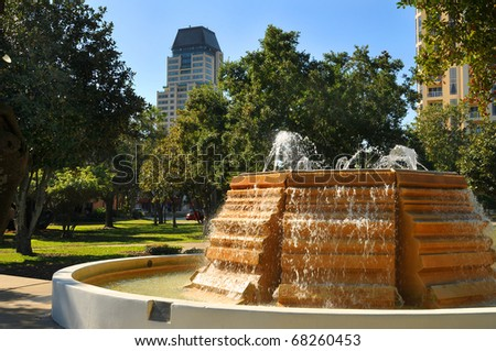 Park located in the business district across from the waterfront in St. Petersburg, Florida. Sidewalks, trees and benches invite people time to reflect and enjoy the beauty of the coastal city. - stock photo