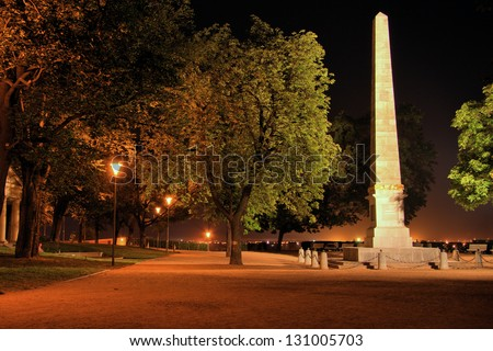 Park path with illuminated obelisk at night, Brno - stock photo