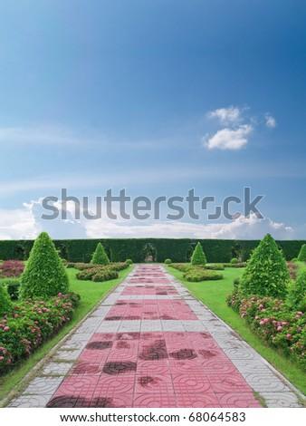 Park pathway among tree surgery in beautiful garden - stock photo