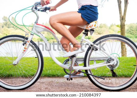 Park ride. Close-up side view of young woman riding bicycle in park - stock photo