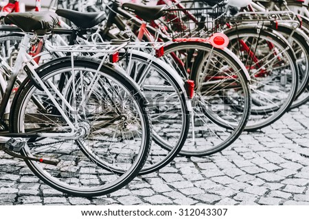 Parked Bicycles On Sidewalk. Bike Bicycle Parking In Big City. Red, Black, White and Red Colors Photo. - stock photo