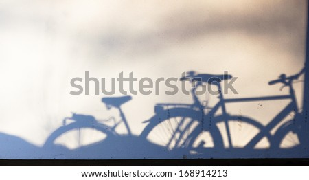 parked bike shadows on wall - stock photo