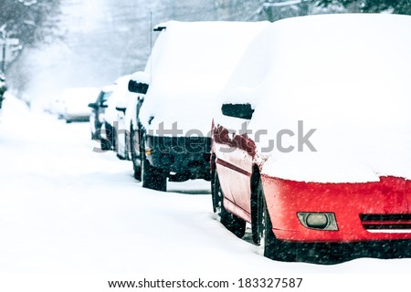 Parked Cars in the Street on a Snowstorm Winter Day - stock photo