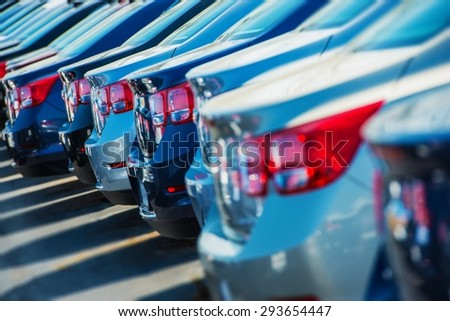 Parked Cars on a Lot. Row of New Cars on the Car Dealer Parking Lot. Cars Market Theme. - stock photo