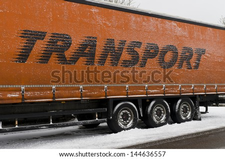 parked trailer in winter with transport written on it - stock photo