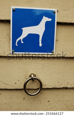 parking for dogs, metal ring and a sign - stock photo