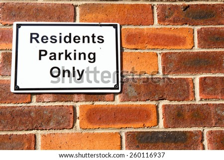 Parking for residents only sign on a brick wall. - stock photo