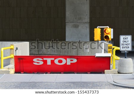 Parking garage exit with stop sign and traffic lamp post - stock photo