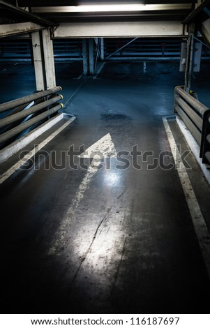 Parking garage in basement, underground interior, arrow sign - stock photo