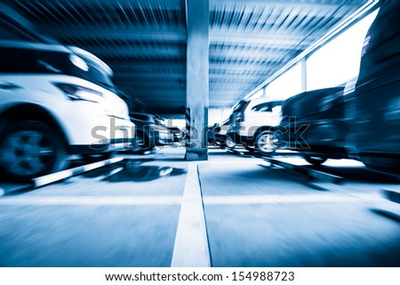 Parking garage, interior with a few parked cars,Motion blur - stock photo