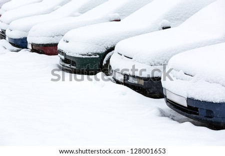 Parking lot with cars covered in fresh snow - stock photo