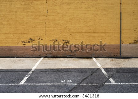 parking place next to a yellow wall - stock photo