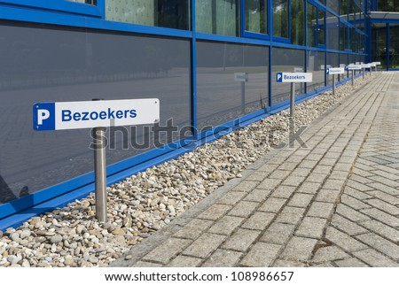 parking places for visitors (bezoekers in dutch) in front of a modern office building - stock photo