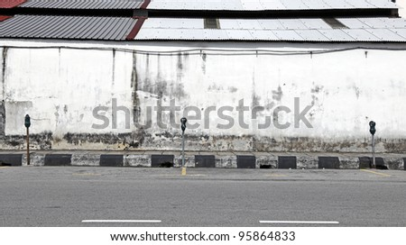Parking spaces with parking meters by a grungy wall along an empty road. - stock photo