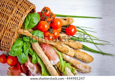 Parma ham prosciutto with grissini bread sticks  - stock photo
