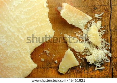 Parmesan cheese in chunks and freshly grated on a rustic wood surface. - stock photo