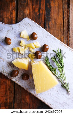 Parmesan cheese on cutting board with sprig of rosemary and olives on wooden table background - stock photo