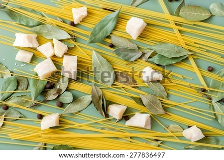 Parmesan cheese, spaghetti, bay leaves and pepper on green background - stock photo