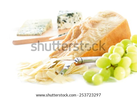 Parmesan cheese wedge with grated shavings and white grapes showing roquefort and danish blue in background on chopping board out of focus  - stock photo