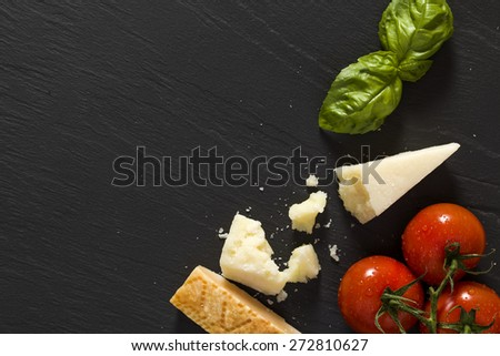 parmigiano tomatoes basil on black background with space for your text - stock photo