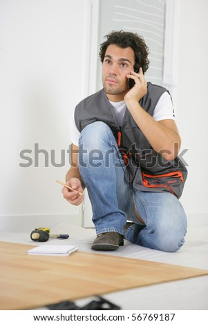 Parquet layer on phone sitting on the floor - stock photo