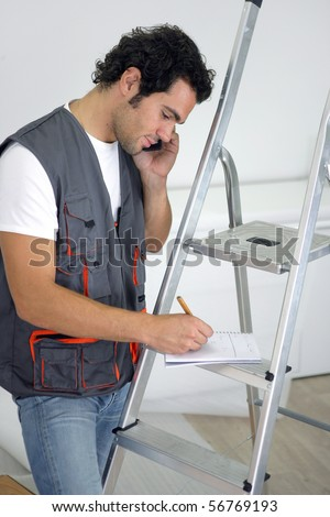 Parquet layer on phone writing on a notepad - stock photo