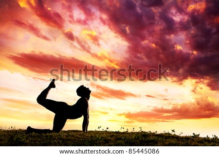 parshva marjariasana cat pose by Man silhouette outdoors at sunset background. Free space for text - stock photo