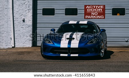 Parsippany,NJ - April 24th 2016: At a free car show, A 2014 Dodge Viper is parked in front of a garage door.  - stock photo