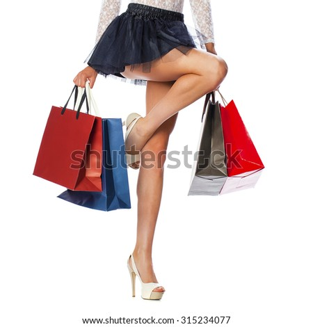 Part body, beautiful female slender legs. Sexy girl holding a paper shopping bags, isolated on white background - stock photo