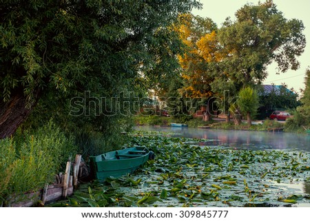 Part if the blue wooden boat on a river overgrown by water lily - stock photo