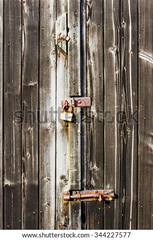 Part of a barn door locked and bolted with weathered wood panels - stock photo