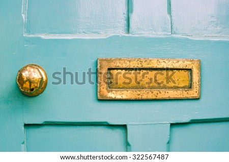 Part of a blue front door with a weathered metal letterbox - stock photo