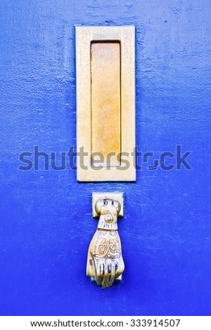 Part of a blue wooden door with an antique metal knocker and letterbox - stock photo