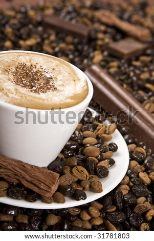 Part of a cup of coffee with chocolate and coffee beans. Selective focus just at the center of the drink. - stock photo