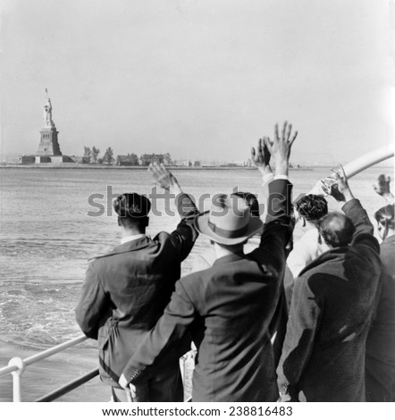 Part of a group of 171 illegal immigrants wave goodbye to Statue of Liberty from Coast Guard cutter that took them from Ellis Island to the Home Lines ship Argentina in Hoboken for deportation. 1952 - stock photo