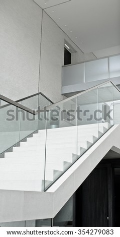 Part of a modern interior staircase with a glass bannister - stock photo