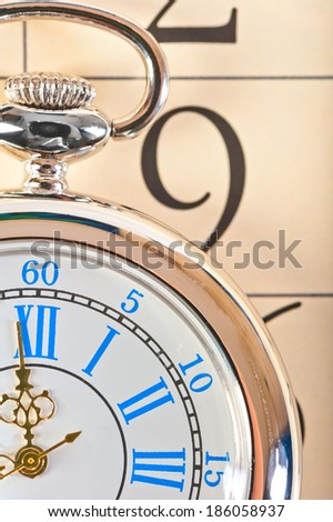 part of a pocket watch lying on the calendar - stock photo