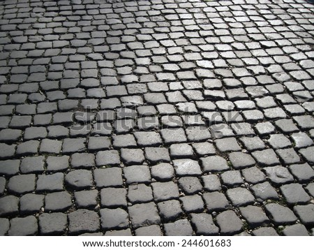 Part of a traditional cobbled street in Rome, Italy, showing hundreds of cobble stones in situ, stretching away into the distance. - stock photo
