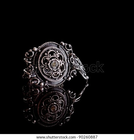 part of a very old bracelet on a black background with reflection - stock photo
