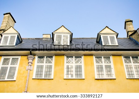 Part of a yellow building in an English town against a bright blue sky - stock photo