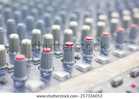 Part of an audio sound mixer with buttons and sliders .  - stock photo
